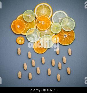 Gesunde Lebensmittel und Medizin Konzept. Pillen von Vitamin C und Zitrusfrüchte in der Form von Wolken und regnet. Zitrusfrüchte geschnittene Limette, Orange und Zitrone