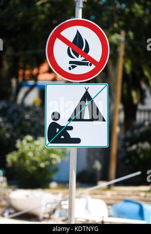 Kein camping und keine Brand Warnschild in Kroatien. Rote und schwarze runde Fire Ban unterzeichnen und grüne Camping - Stockfoto