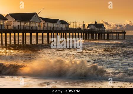 An einem stürmischen morgen Anfang August der Himmel wird orange als die Sonne hinter den Pier in der beliebten - Stockfoto