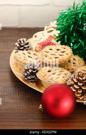 Weihnachten Mince Pies auf einen goldenen Schild mit weißem Rentier auf ein Holz Hintergrund - Stockfoto