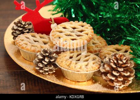 Weihnachten Mince Pies auf ein goldenes Schild mit rotem Rentier auf ein Holz Hintergrund - Stockfoto