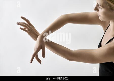 Elegante Ballerina posiert im Studio auf dem hellen Hintergrund. Sie hält ihre Arme in der Luft vor sich gekreuzt. - Stockfoto