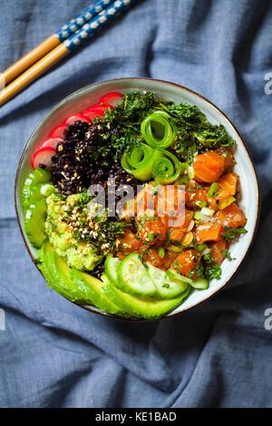 Lachs ahi Poke mit Schwarzen verboten, Reis, Gurken, Avocado und Radieschen - Stockfoto