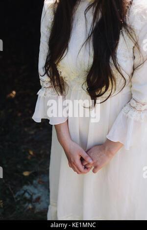 Ein Mädchen mit langen braunen Haaren trägt ein Vintage White Kleid mit ihren gefalteten Händen vor ihr, Großbritannien - Stockfoto