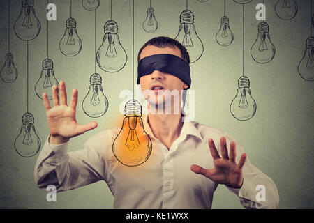 Mit verbundenen Augen junger Mann zu Fuß durch Glühbirnen auf der Suche nach hellen Idee - Stockfoto