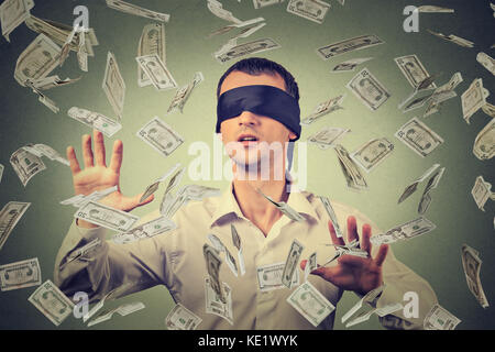 Mit verbundenen Augen junger Geschäftsmann versucht, Dollar, Rechnungen zu fangen Banknoten fliegen in der Luft - Stockfoto