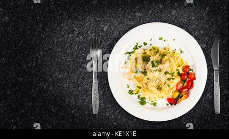 Frische hausgemachte Bandnudeln mit Waldpilzen, Petersilie und Cherry Tomaten Salat auf Granit Küchenarbeitsplatte. - Stockfoto