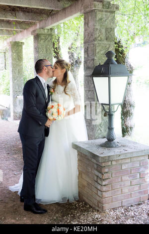 Schöne Braut und Bräutigam am Tag der Hochzeit gehen im Freien auf Frühling Natur. Brautpaar , frisch verheiratete - Stockfoto