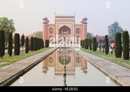 Das taj mahal Mausoleum Tor dominiert eine reflektierte Perspektive über einen Wasser spiegel bei Sonnenaufgang, - Stockfoto