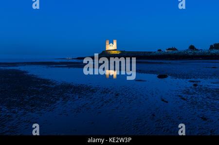 Reculver Towers leuchtet in der Dämmerung an der Küste von Kent - Stockfoto
