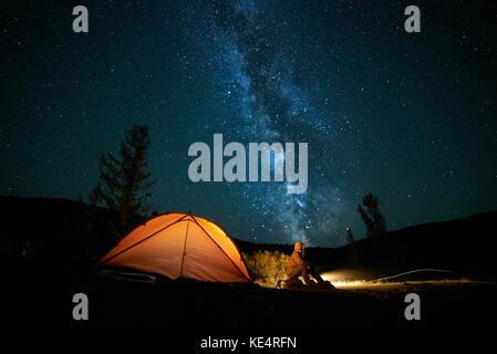 Mann Tourist in der Nähe seiner camp Zelt in der Nacht. - Stockfoto