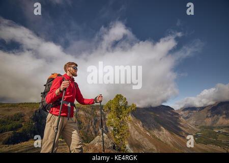 Hübscher junger Bartgeier Wanderer sitzen am Rande einer Schlucht weg schauen - Stockfoto
