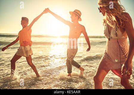 Verspielte junge Freunde Plantschen im sonnigen Sommer Ocean Surf - Stockfoto