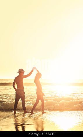 Junges Paar Hände halten, wandern auf sonnigen Sommer Sunset Ocean Beach - Stockfoto
