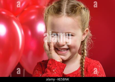 Valentinstag Mädchen im roten Kleid mit einem roten Herzen. - Stockfoto