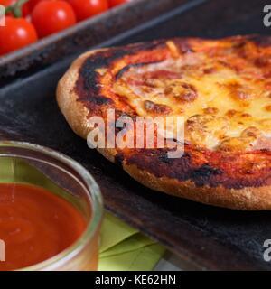 Hausgemachte glutenfreie Pizza Schinken und Käse, gut gemacht und knusprig, mit Kirschtomaten und Schüssel von Ketchup