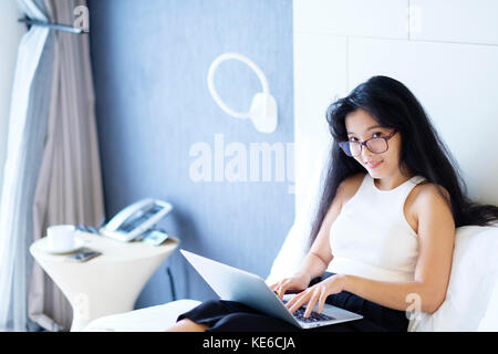 Junge asiatische Geschäft Frau in ihrem Hotelzimmer arbeiten - Stockfoto