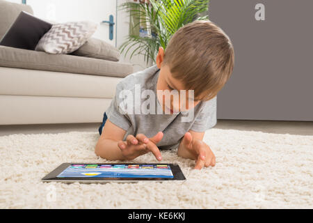 Junge liegend auf dem Teppich mit digitalen Tablet mit mehrfarbigen Anwendungen damit - Stockfoto