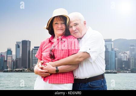 Portrait Of Happy senior Paar umarmen vor Hong Kong Skyline der Stadt. - Stockfoto