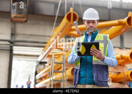 Schweren männlichen Techniker mit digitalen Tablet in der Factory - Stockfoto