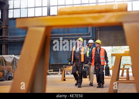 Männliche Arbeitskräfte wandern in Stahlwerk - Stockfoto