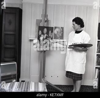 1960, historische, inneres Bild, eine Dame das Tragen einer Schürze Malerei Stillleben Blume Bild mit Ölen, auf - Stockfoto
