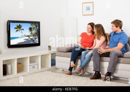 Glückliches Paar sitzt auf einem Sofa mit ihrer Tochter vor dem Fernseher zu Hause - Stockfoto