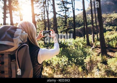 Frau machen Fotos mit dem Handy während des Trekking. Wanderer mit Rucksack fotografieren Wald Szenen. - Stockfoto