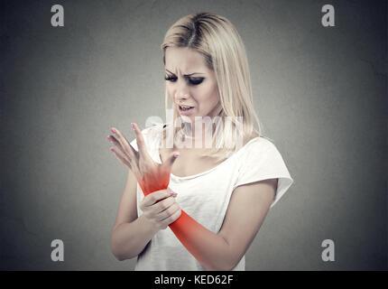 Frau ihre schmerzhafte Handgelenk auf grauen Hintergrund isoliert halten. Verstauchung Schmerz Lage durch roten - Stockfoto