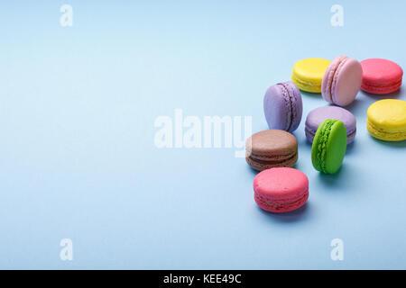 Bunte Makronen auf blauem Papier Hintergrund. Süße macarons. Kopieren Sie Platz für Ihren Text. - Stockfoto