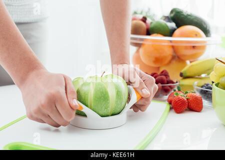 Frau Vorbereiten eines leckeren veganen Snack in Ihrer Küche mit Obst, sie ist das Schneiden einer organischen Green - Stockfoto