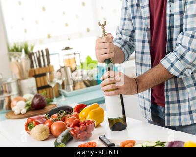 Man öffnet eine Flasche Wein in der Küche, er ist mit einem Korkenzieher - Stockfoto