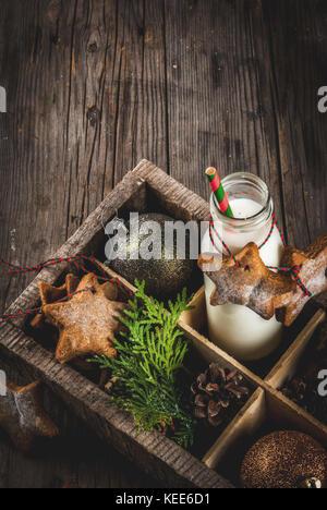 Weihnachten Süße und behandelt, Flasche mit Milch für Santa mit Lebkuchen star Cookies mit Dekoration Seil und Weihnachtsschmuck, - Stockfoto