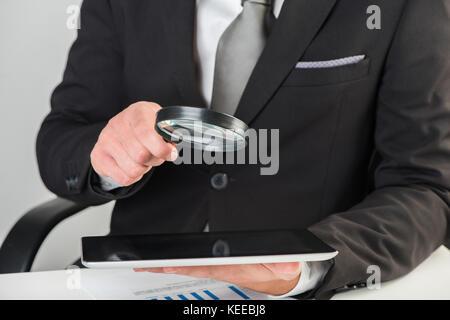 Unternehmer die Kontrolle einer Tablette mit Lupe - Stockfoto