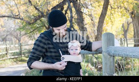 Tausendjährige Vati mit Baby im Träger außerhalb zu Fuß - Stockfoto