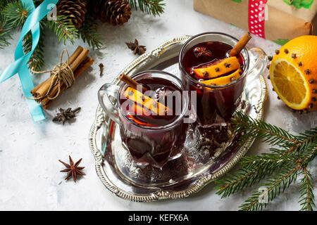 Hausgemachte Weihnachten cocktail Glühwein Rotwein mit Zimtstangen, Orangen und Nelken, in zwei Tassen serviert - Stockfoto