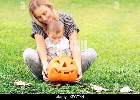 Schöne junge Mutter mit entzückenden kleinen Kind, spielend mit geschnitzten Kürbis, genießen Sie traditionelle - Stockfoto