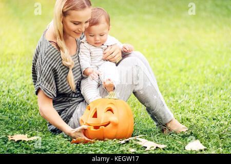 Glückliche Mutter und Baby boy draussen, sitzen auf der grünen Wiese mit orange geschnitzten Kürbis dekorative Spielzeug, - Stockfoto
