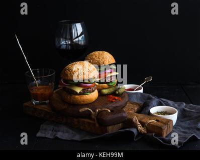 Frisches Rindfleisch Burger auf rustikalen hölzernen Brettern mit einem Glas Wein und Tomatensauce, schwarzer Hintergrund, - Stockfoto
