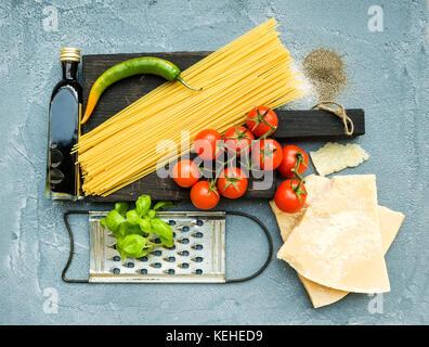 Zutaten für Kochen Pasta. Spaghetti auf dunklen Holzplatte, Parmesan, Tomaten, metallreibebrett, Olivenöl und frischem - Stockfoto