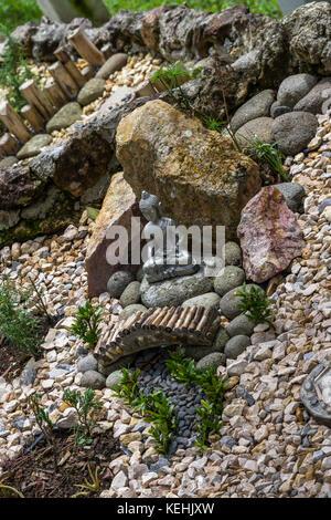 Garten Ideen Zen Stone Garten mit kleiner sitzender Buddha Statue - Stockfoto