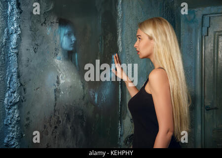 Junge Frau schaut in den Spiegel und sehen in der Reflexion ein Geist Mädchen Angst - Stockfoto