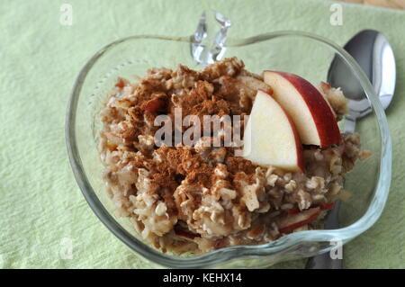 Gesundes Frühstück - Haferflocken mit geriebenem Apfel und zerdrückte Banane mit Zimt bestreut - Stockfoto