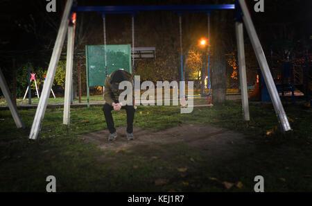Single Mann mit gesenktem Kopf auf einer Schaukel in einem Park außerhalb in der Nacht in der Stadt, das Konzept - Stockfoto