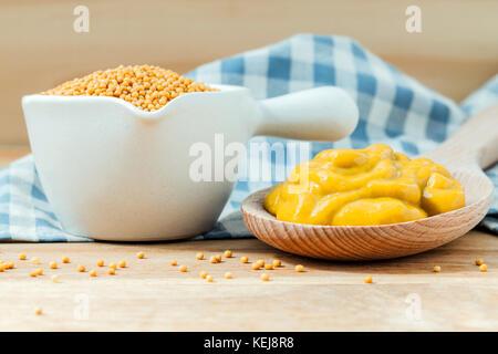 Zusammensetzung der Senf auf Holzlöffel und Senfkörner in Keramik Schüssel setup auf Holz- Hintergrund. - Stockfoto