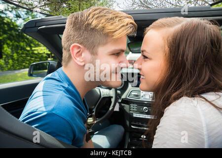 Glückliches junges Paar in einem Auto an jeder anderen Suchen sitzen - Stockfoto