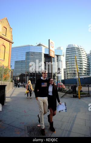 Glücklich lächelnde kaukasischen Mann & asiatische Frau zu Fuß mit der Waffe in London um einander, England - Stockfoto