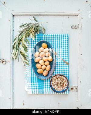 Grüne große Oliven in blau Keramik Platte mit Ast und Gewürzen auf Küchenpapier auf hellblauem Hintergrund, Ansicht - Stockfoto