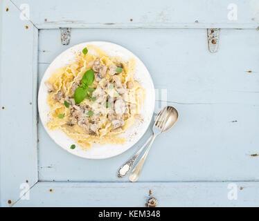 Pasta Mafaldine mit Pilzen und Sahnesauce aus weisser Keramik Platte über hellblau Holz- Hintergrund. top View. - Stockfoto