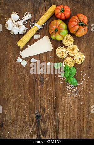 Zutaten zum Kochen Pasta Spaghetti, Tagliatelle, Knoblauch, Parmesan, Tomaten und frischem Basilikum auf rustikalen - Stockfoto